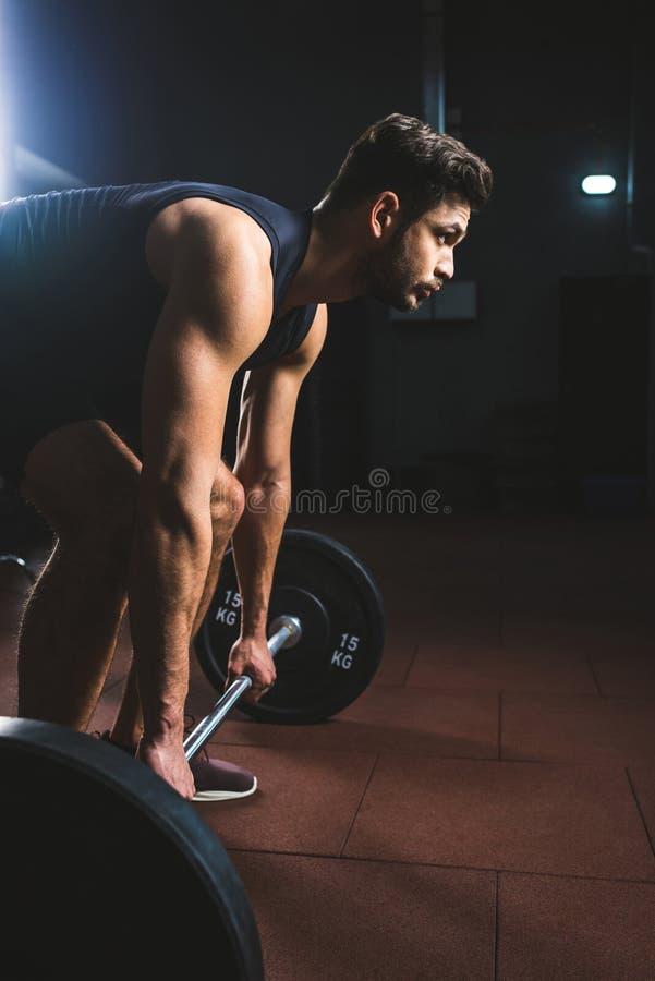 Sidosikt av den unga idrottsman nen som förbereder sig att lyfta skivstången arkivbild