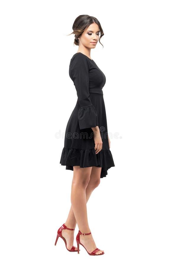 Sidosikt av den unga kvinnan i den svarta klänningen som ner står och ser arkivfoton