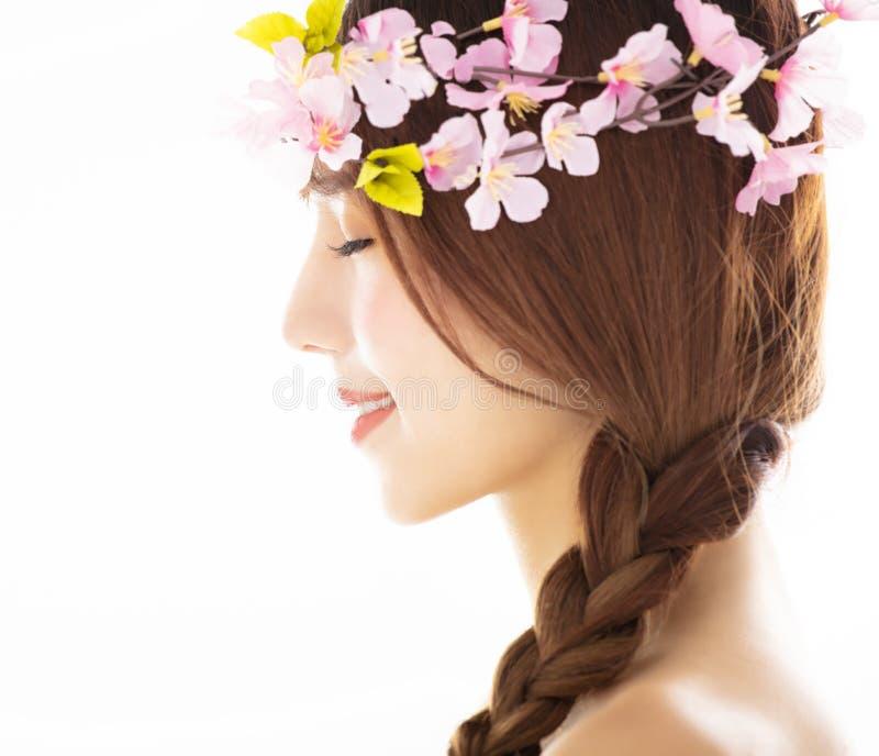 Sidosikt av den unga le skönhetframsidan med blomman royaltyfria foton
