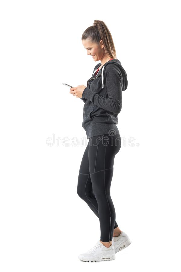 Sidosikt av den unga lyckliga passformlöparekvinnan som använder mobiltelefonen och att le arkivbilder
