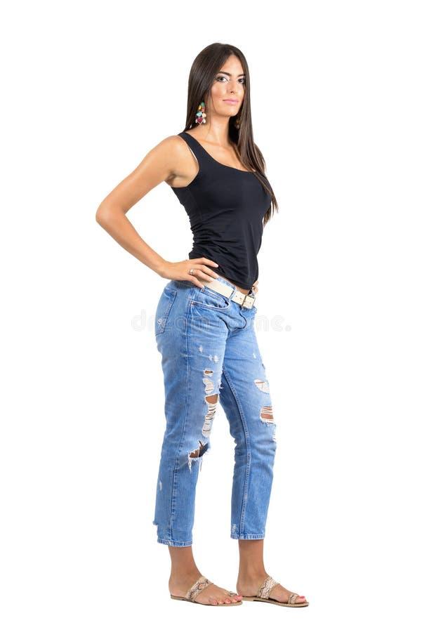 Sidosikt av den unga säkra latinamerikanska kvinnlign som poserar på kameran med handen på hennes höft fotografering för bildbyråer