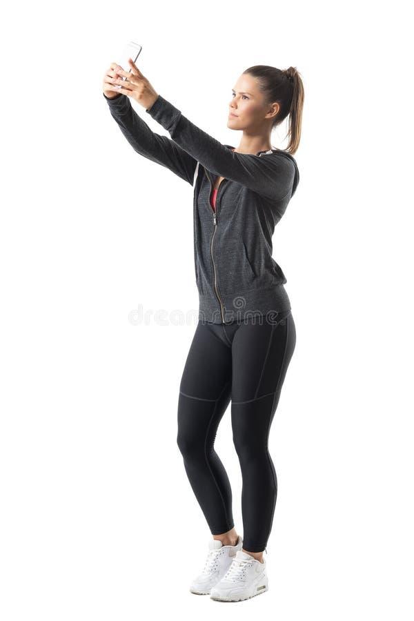 Sidosikt av den unga säkra stolta aktiva sportiga kvinnan som tar selfie som ser telefonen arkivbild