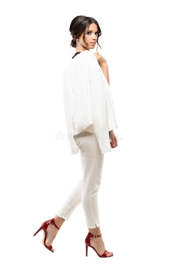 Sidosikt av den ursnygga eleganta affärskvinnan i den vita dräkten som går och ser kameran royaltyfria foton