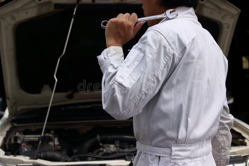 Sidosikt av den yrkesmässiga unga mekanikermannen i enhetlig innehavskiftnyckel mot bilen i öppen huv på reparationsgaraget arkivbild