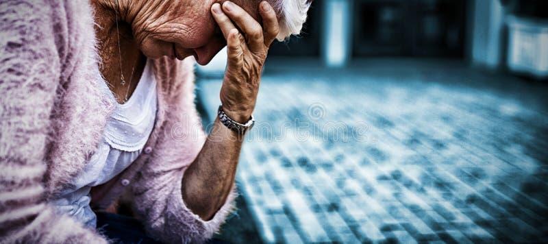 Sidosikt av deprimerat högt kvinnasammanträde på bänk med huvudet i hand royaltyfria foton
