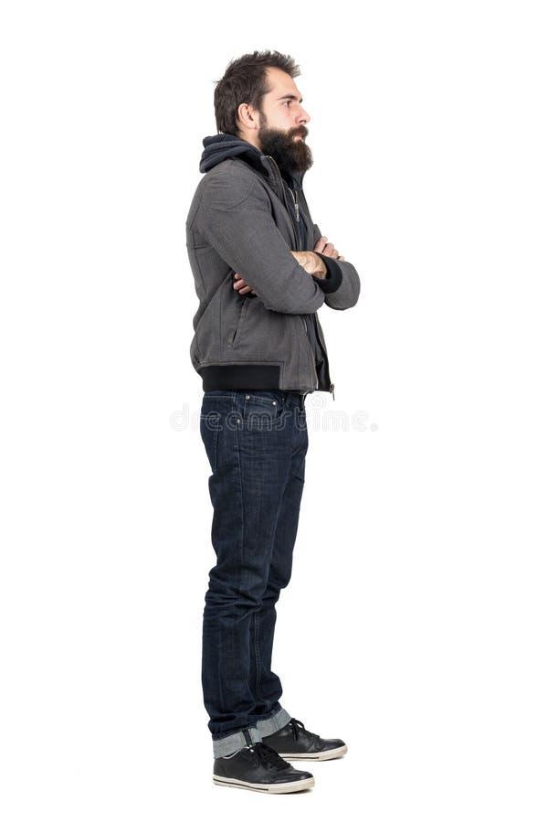 Sidosikt av det bärande omslaget för skäggig man över den med huva tröjan med korsade armar som bort ser arkivfoton