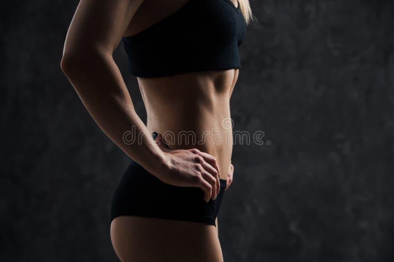 Sidosikt av det kvinnliga modellanseendet för muskulös kondition på svart bakgrund Bärande sportbehå för ung kvinna som ner in se arkivfoto
