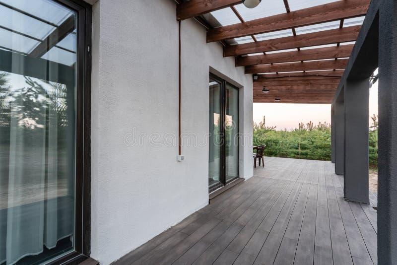 Sidosikt av en öppen veranda framme av en modern skogstuga Sörja den unga skogen under solnedgångstrålarna i fotografering för bildbyråer