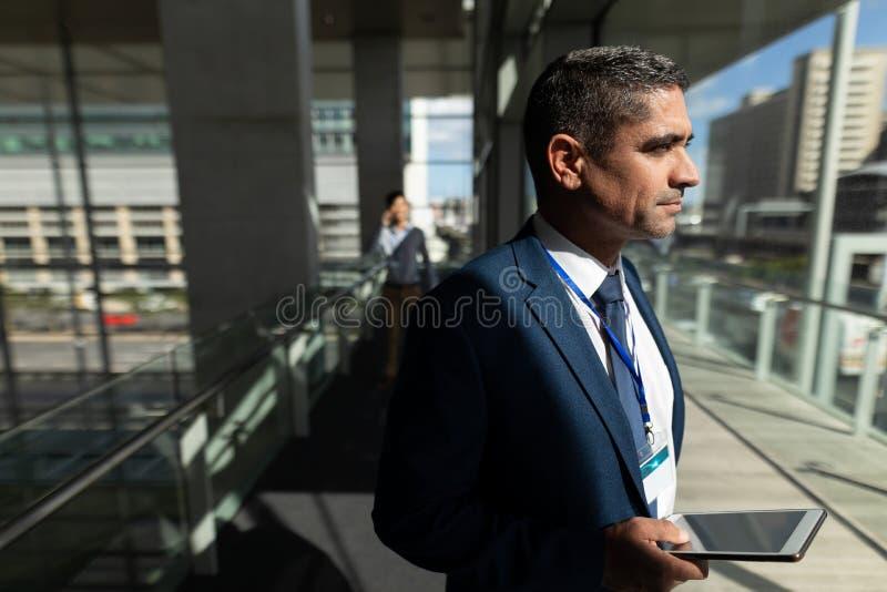 Sidosikt av en affärsman som rymmer en digital minnestavla och bort ser genom hela fönster arkivfoto
