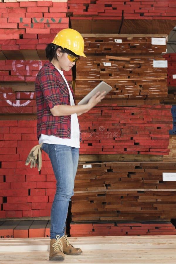 Sidosikt av en asiatisk kvinnlig industriarbetare som använder minnestavlaPC med staplade träplankor i bakgrund royaltyfri fotografi