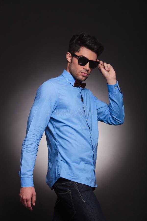 Sidosikt av en attraktiv ung man som fixar hans solglasögon royaltyfria bilder