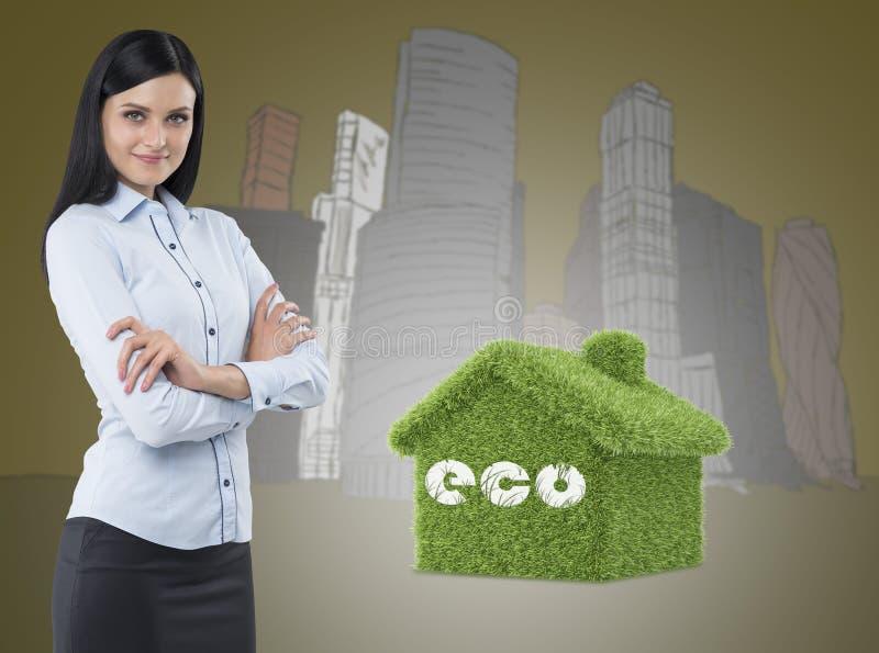 Sidosikt av en fundersam kvinna med korsade händer Det gröna huset och skyskrapor är på bakgrund royaltyfria bilder
