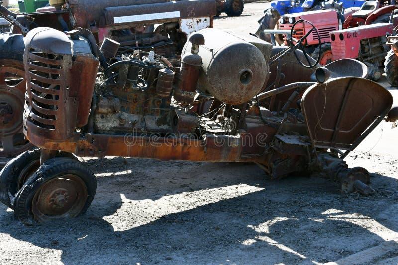 Sidosikt av en gammal övergiven rostig jordbruks- traktor arkivfoto