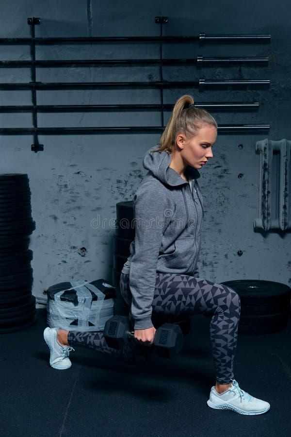 Sidosikt av en härlig konditioninstruktör för ung kvinna som bär en sportdräkt som gör på utfall för en övning med hantlar royaltyfri foto