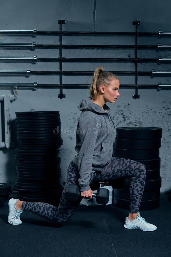 Sidosikt av en härlig konditioninstruktör för ung kvinna som bär en sportdräkt som gör på utfall för en övning med hantlar arkivfoto