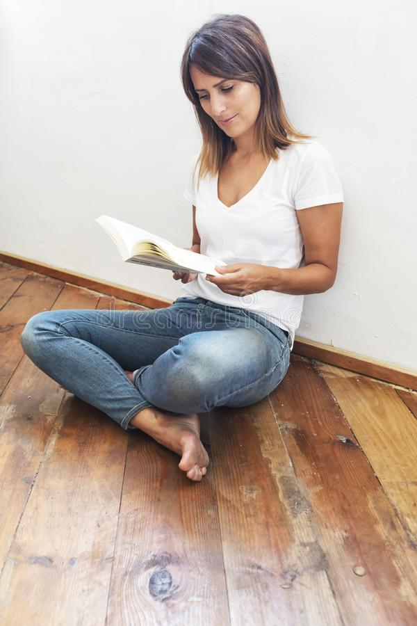Sidosikt av en h?rlig kvinna som sitter p? jordning som lutar p? en vit v?gg, medan l?sa en bok arkivfoto