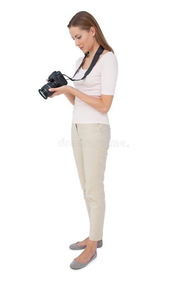 Sidosikt av en härlig kvinnlig fotograf royaltyfria bilder