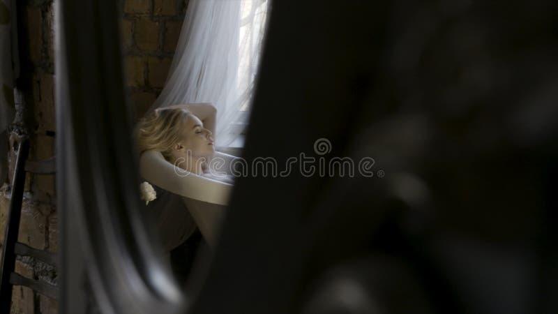 Sidosikt av en härlig ung blond kvinna som kopplar av i badruminre och trycker på hennes hår i spegelreflexionen arkivfoton