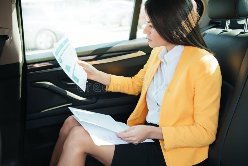 Sidosikt av en koncentrerad affärskvinna som analyserar dokument arkivfoto