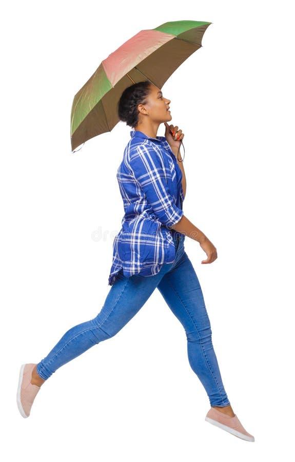 Sidosikt av en kvinna som balanserar med ett paraply flickan hoppar över en pöl arkivfoton