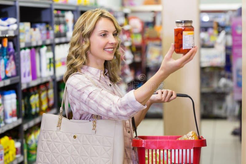 Sidosikt av en le nätt blond kvinna som ser en produkt royaltyfri bild