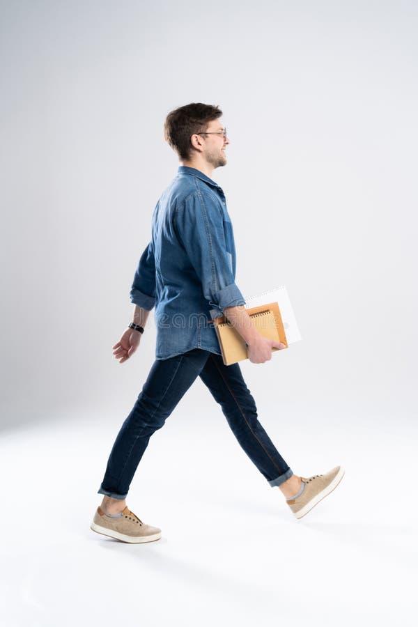 Sidosikt av en le ung tillfällig man som går, student med bokang-anmärkningar på vit bakgrund arkivbild