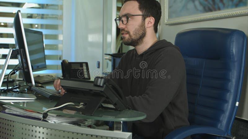 Sidosikt av en manlig kontorsarbetare som arbetar på datoren i ett ljust kontor royaltyfria bilder