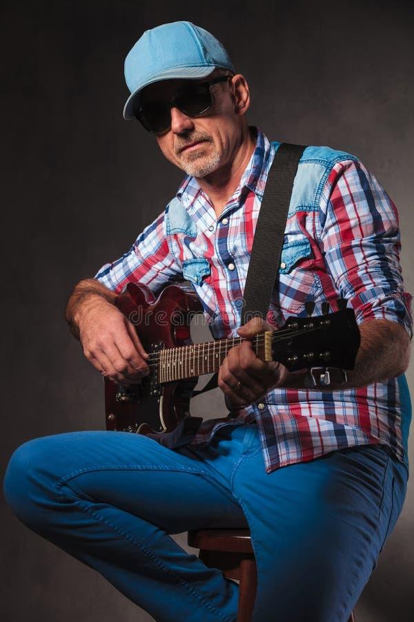 Sidosikt av en mogen man som spelar en elektrisk gitarr arkivfoto