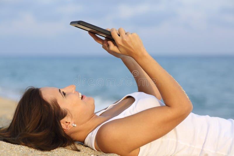 Sidosikt av en tonåringflicka som bläddrar hennes minnestavlaPC som ligger på sanden av stranden arkivbilder