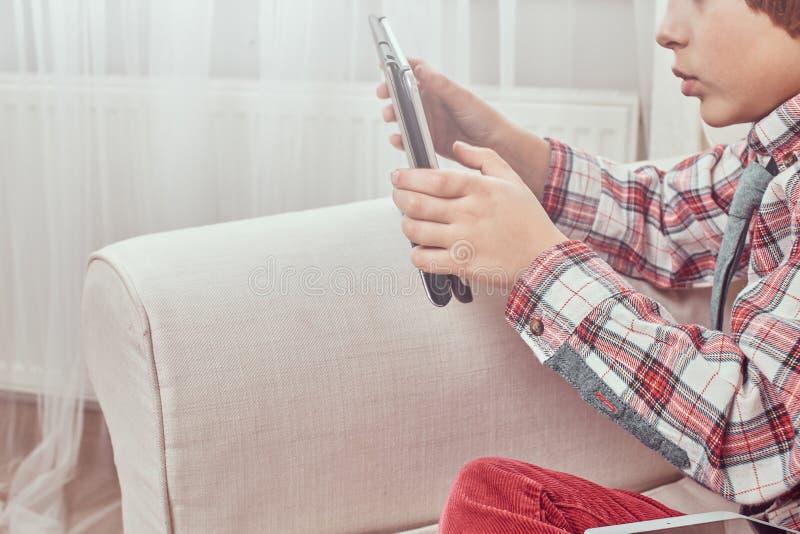 Sidosikt av en ung Caucasian skolpojke som bär en rutig skjorta med bandet genom att använda en digital minnestavla som sitter på royaltyfri foto