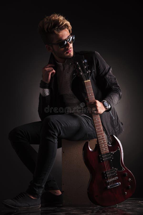 Sidosikt av en ung gitarrist som tillbaka sitter och ser arkivbilder