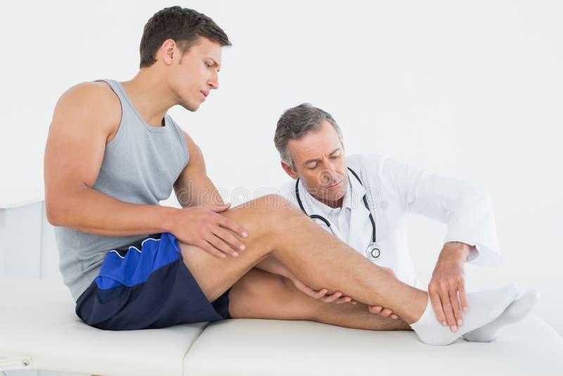 Sidosikt av en ung man som får hans ben undersökt arkivfoto