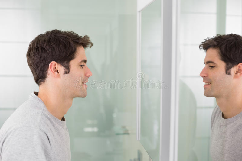 Sidosikt av en ung man som ler på själven i badrumspegel royaltyfri foto