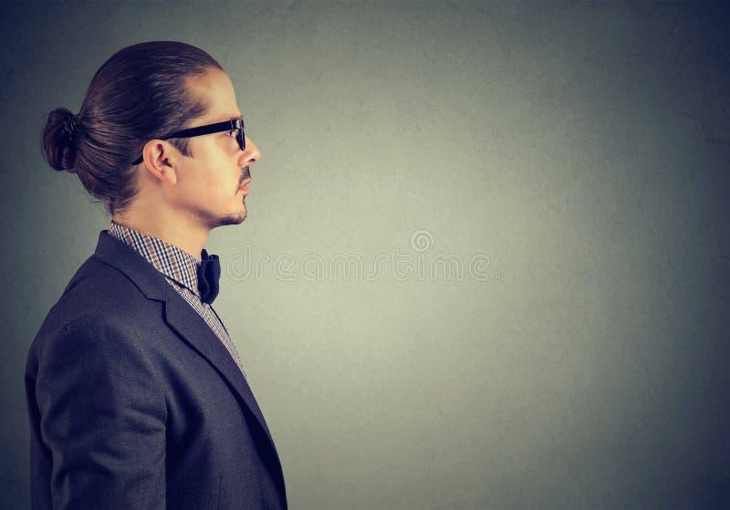 Sidosikt av en vuxen man i dräkten som ser allvarlig på grå bakgrund arkivbild