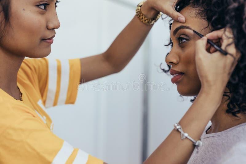 Sidosikt av en yrkesmässig makeupkonstnär som markerar ögonbryn av en modell makeupkonstnär som förbereder modellen för en fotofo royaltyfri bild