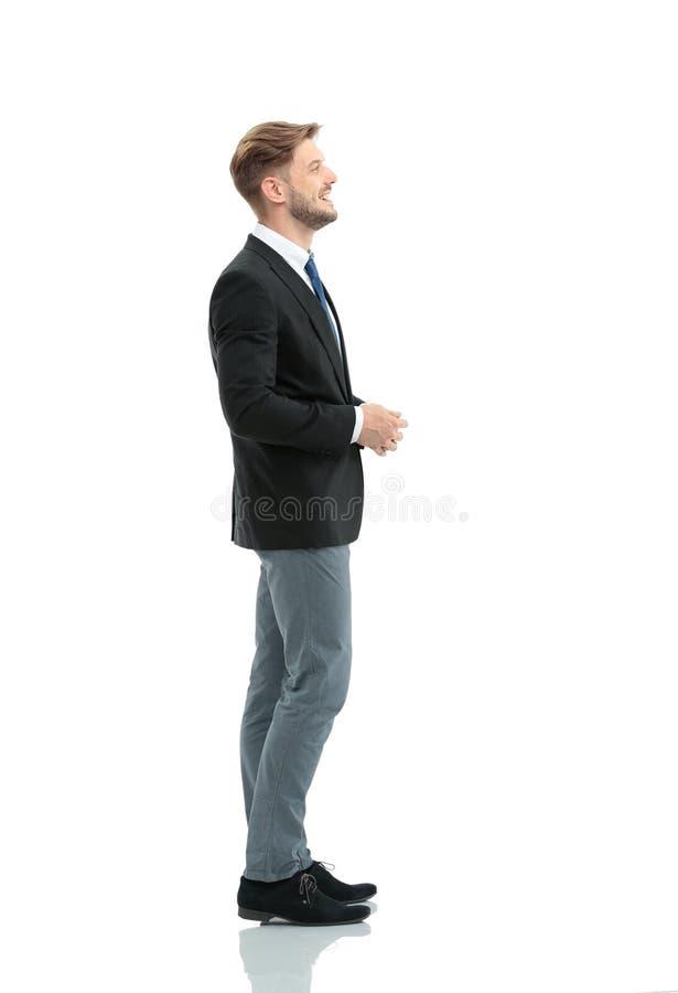 Sidosikt av ett le affärsmananseende, på vit backgroun fotografering för bildbyråer