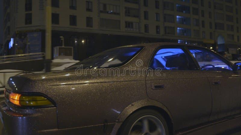Sidosikt av ett modernt medel med härligt purpurfärgat glänsande flytta sig för bilkroppbeläggning som är snabbt i staden på natt arkivbilder