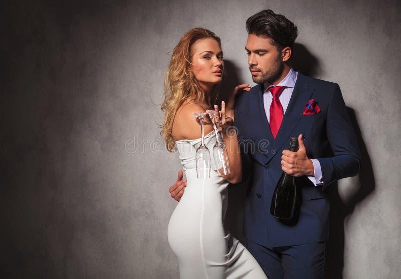 Sidosikt av ett varmt par som rymmer en flaska av champagne royaltyfri bild