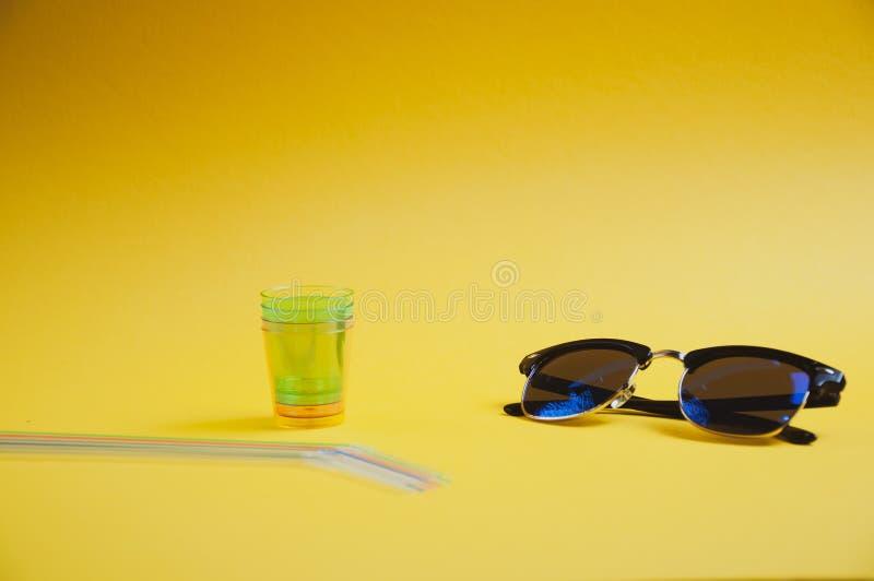 Sidosikt av färgrika sugrör, exponeringsglas och solglasögon på gul bakgrund, med kopieringsutrymme royaltyfri bild