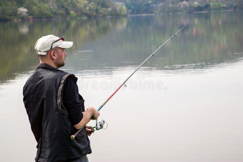 Sidosikt av fiskaren Reeling String And som kastar Rod In The Calm Lake fotografering för bildbyråer