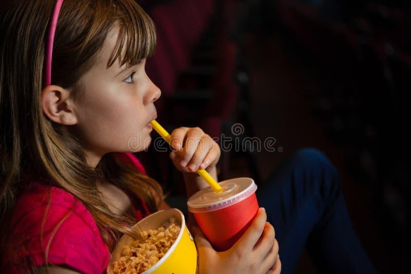 Sidosikt av flickan som har drinken och popcorn under film royaltyfria bilder