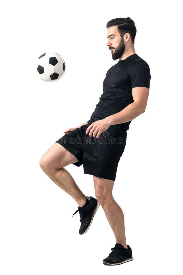 Sidosikt av fotboll eller den futsal spelaren som jonglerar bollen med hans knä fotografering för bildbyråer