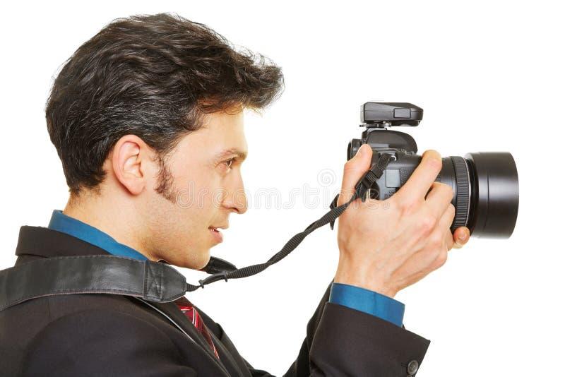 Sidosikt av fotografen som tar bilder royaltyfri foto
