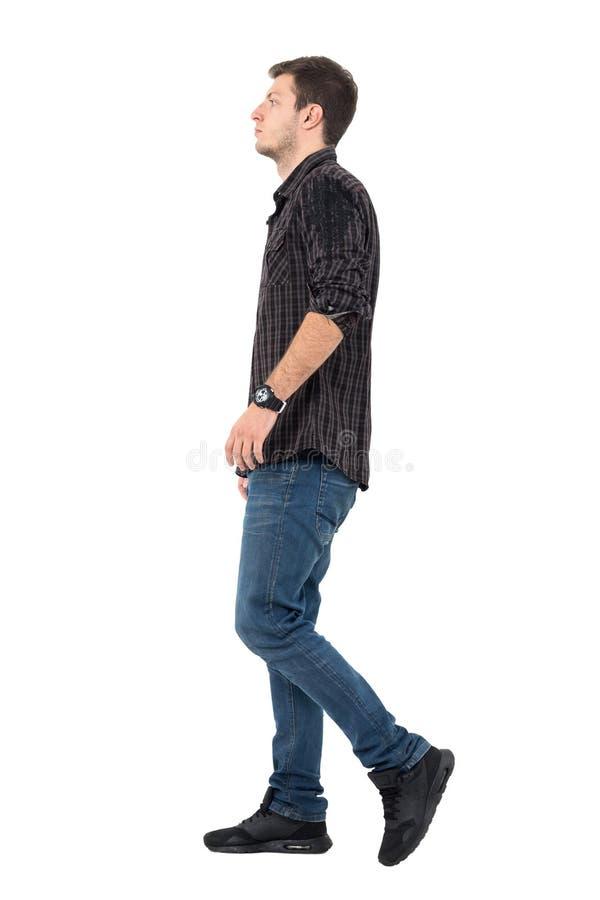 Sidosikt av gå för jeans och för skjorta för ung man bärande royaltyfri bild