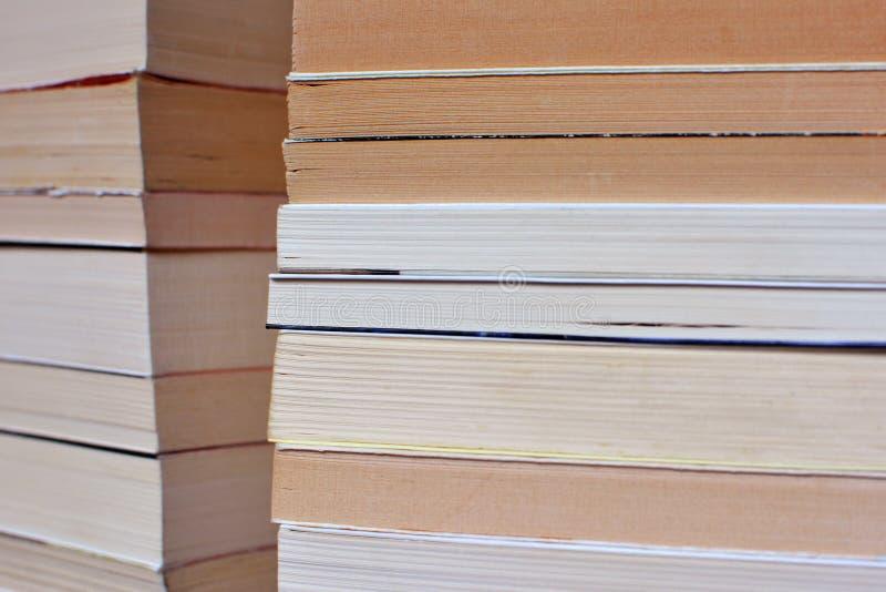 Sidosikt av hörnet av åtskilliga gamla staplade böcker royaltyfri bild