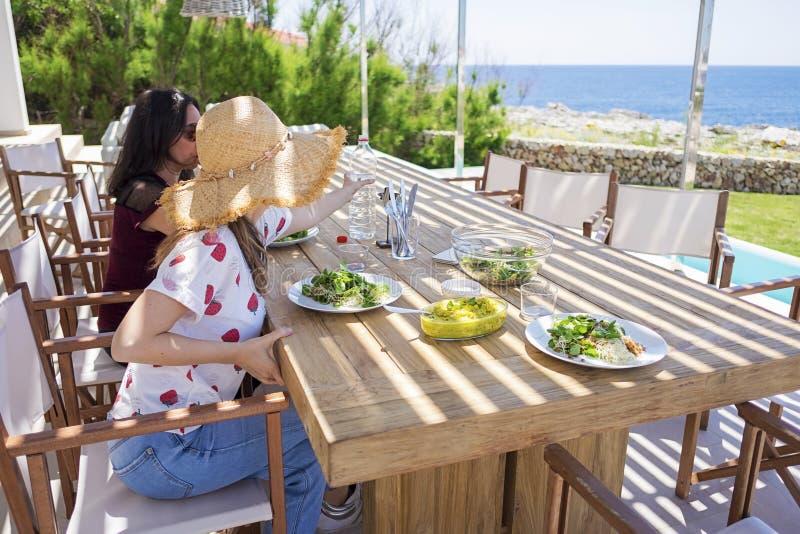 Sidosikt av kvinna som tv? sitter, medan ha en sund matst?lle framme av havet royaltyfri bild