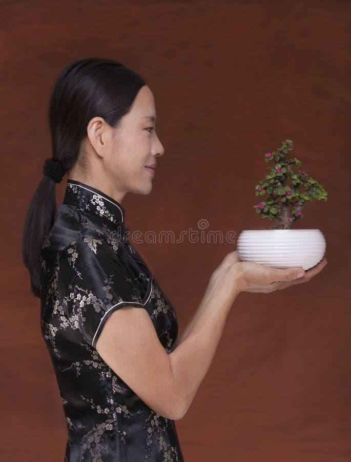 Sidosikt av kvinnan i traditionella kläder som rymmer en liten växt i en blomkruka, studioskott arkivfoto