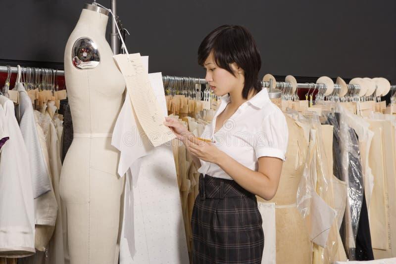 Sidosikt av kvinnan som arbetar i hennes klädlager royaltyfri foto