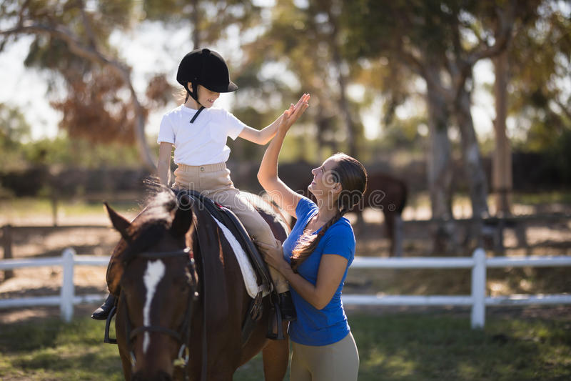 Sidosikt av kvinnan som ger höjdpunkt fem till flickasammanträde på häst royaltyfri bild