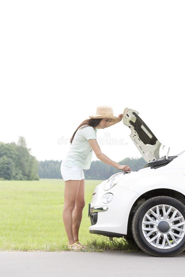 Sidosikt av kvinnan som ner undersöker den brutna bilen på landsvägen royaltyfri bild